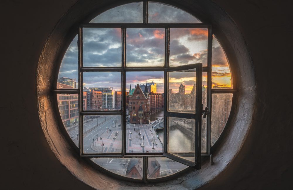 Blick durch ein altes Fenster auf die Speicherstadt und die Elbphilharmonie in Hamburg. Foto: Kerstin Bittner