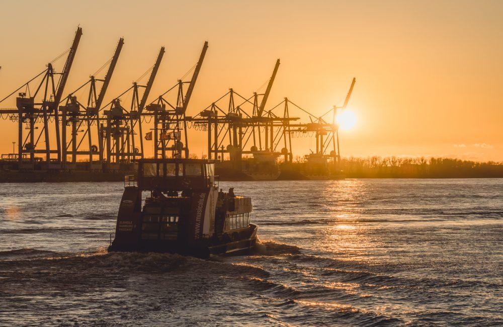 Hafenfähre in Hamburg fährt auf der Elbe in den Sonnenuntergang. Foto: Kerstin Bittner